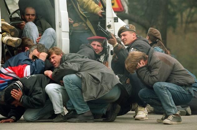 Populares abrigam-se dos primeiros disparos. Note-se a presença de dois elementos da milícia da cidade.