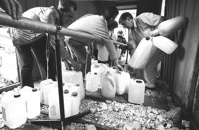 Habitantes de Sarajevo abastecem-se de água na Sarajevska durante o cerco